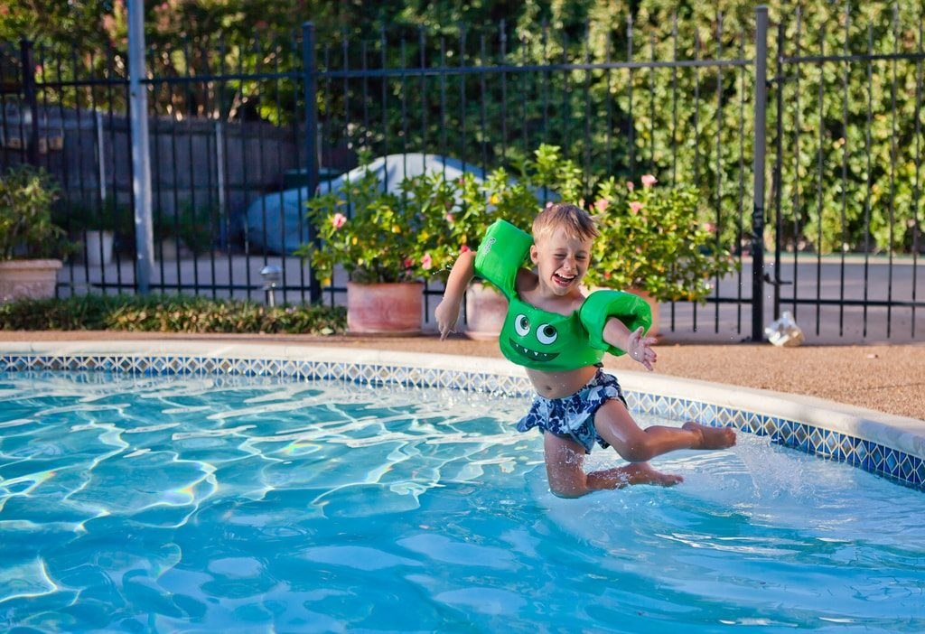 Kid in water wings jumping into a pool.